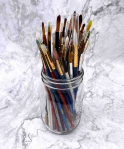 various artists brushes in a mason jar on a white background