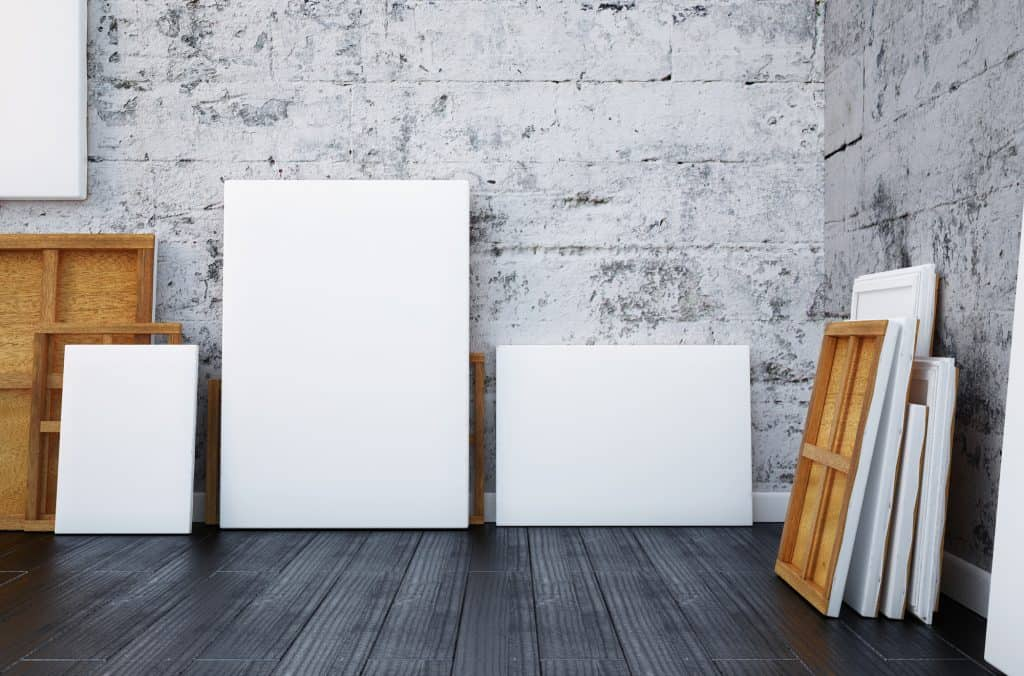 several blank artists canvases against the wall