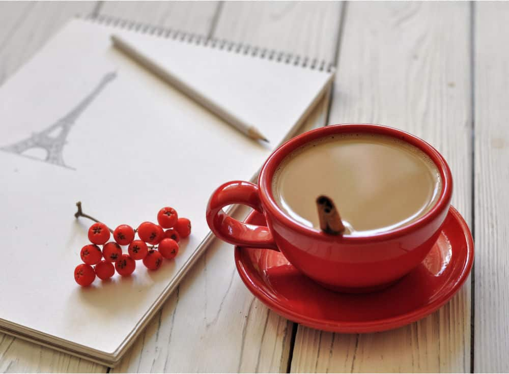 red coffee cup with coffee and cinnamon stick and drawing pad and pencil with drawing of the Eiffel Tower