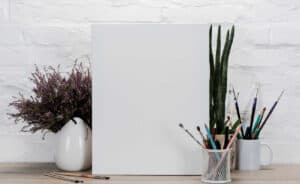 blank canvas with vase of flowers and paint brushes in a jar