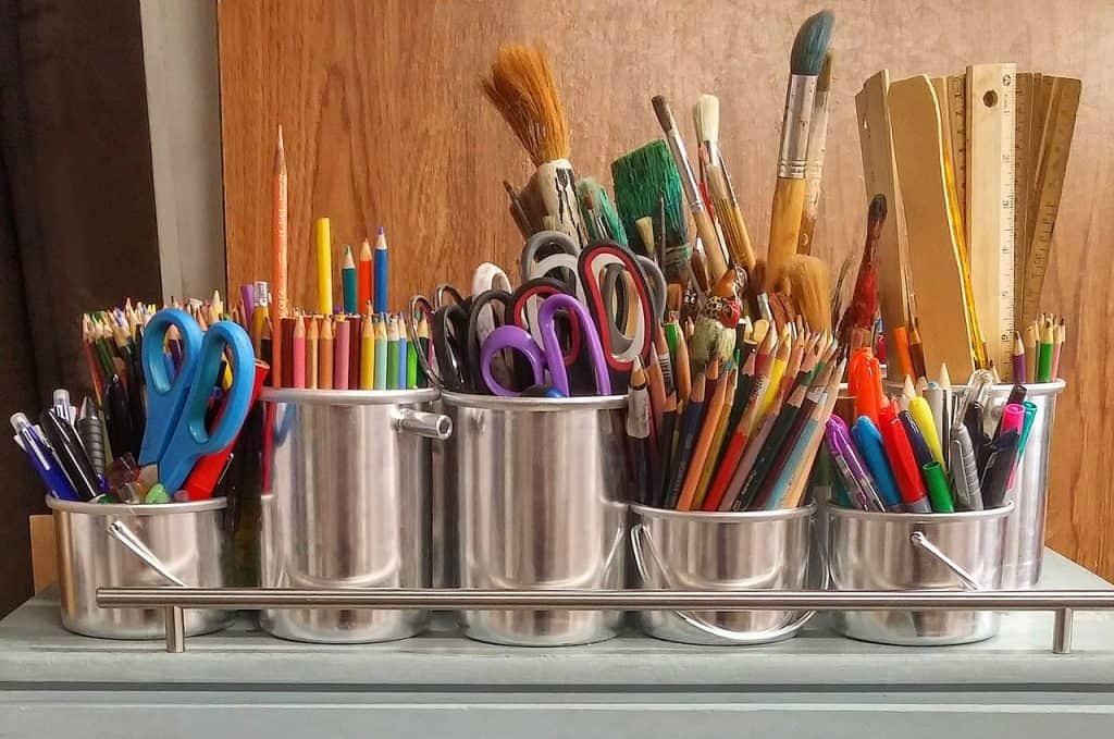 artist brushes, pencils, scissors and rulers in metal jars organized artist