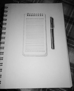graphite drawing of a notebook and pen