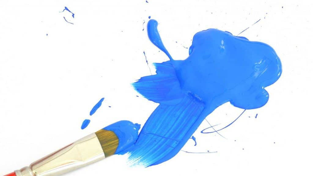paint brush and splatter of blue acrylic paint