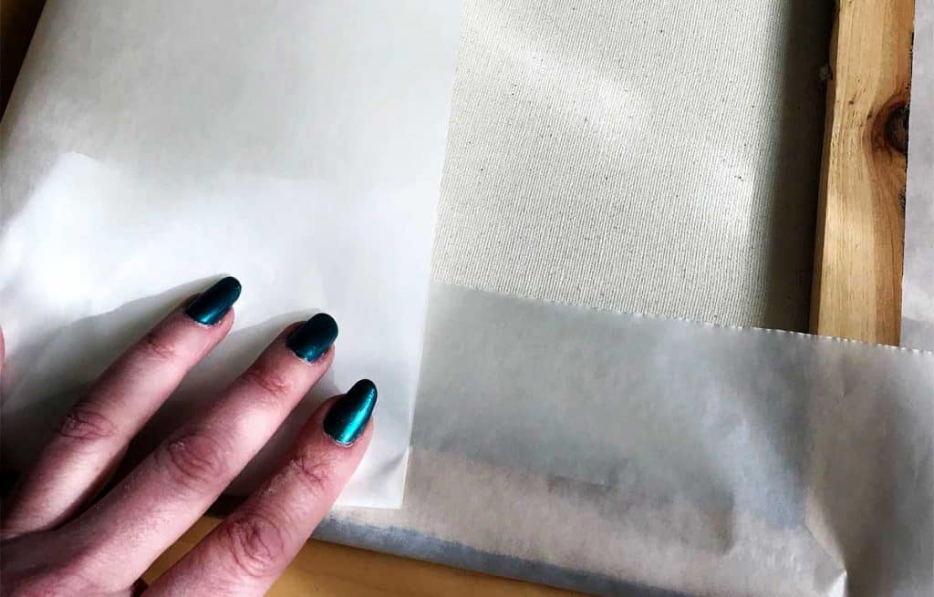 Wrapping an artists canvas in glassine.