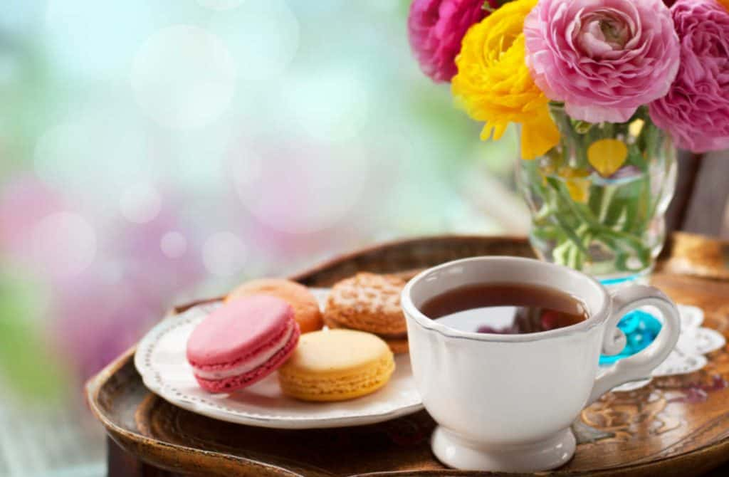 coffee in a white coffee cup, a plate of macaroons and a vase of flowers on brown tray.
