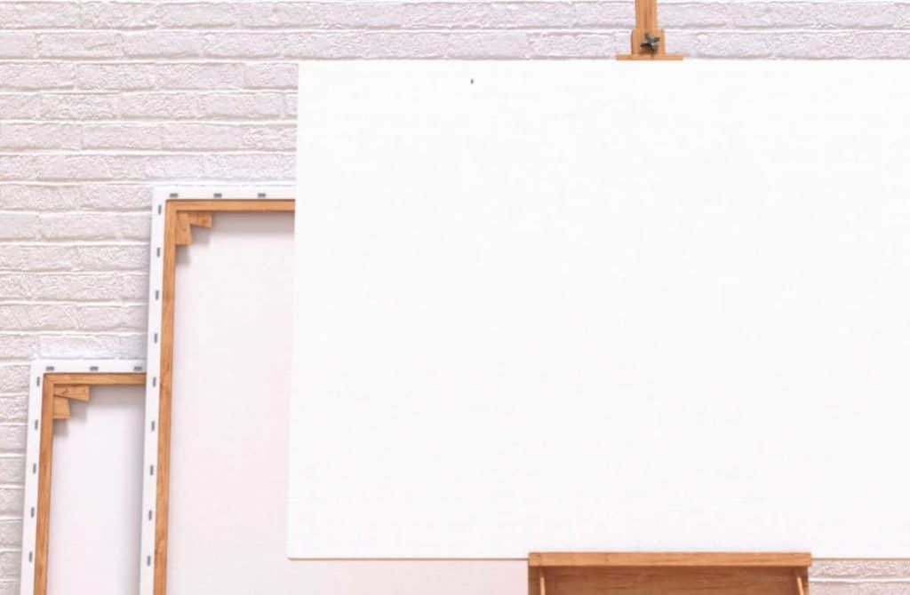 Two blank artist canvases against a wall and one on an easel