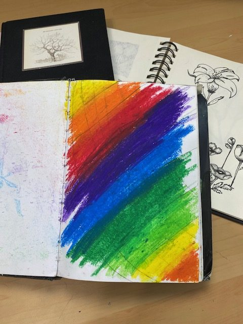 journals with rainbow colored background and pen and ink flowers.