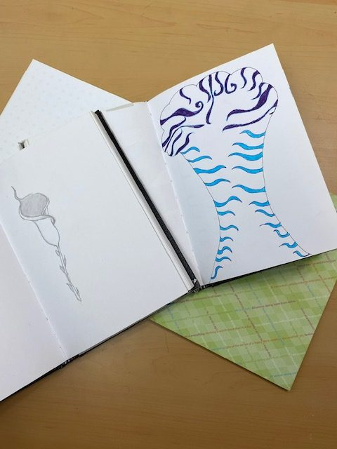 sketchbook with drawing of a calla lily in graphite and an abstract shape in blue marker.