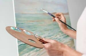 artist painting at an easel holding a palette and brush