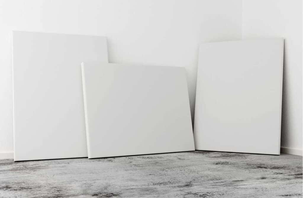 three blank artists canvases leaning against a white wall