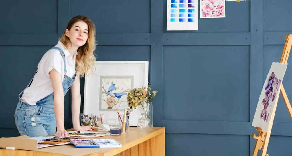 artist working at her desk surrounded by paints, easels and paintings