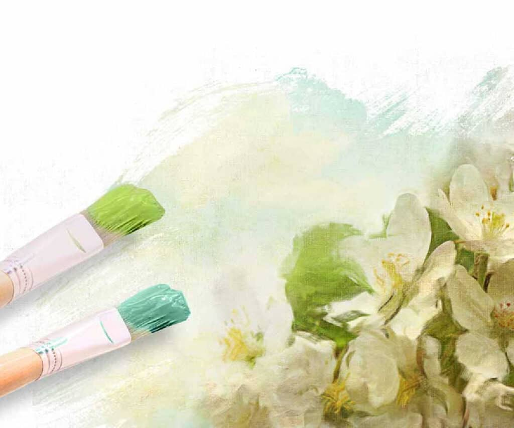 painting in progress of white flowers with two paintbrushes containing blue and green paint