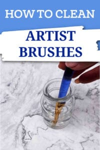 artist cleaning a brush with a blue handle in a small jar of isopropyl alcohol on a marble background