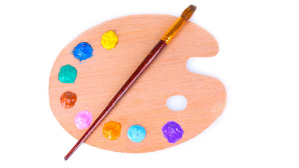 artists wooden palette with blobs of various colored paint and a red paint brush