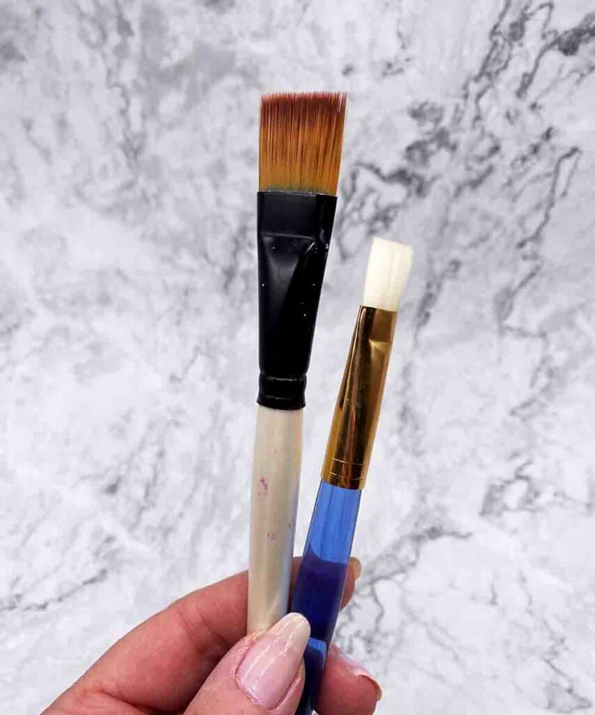 two synthetic artist brushes, one with white handle and brown bristles and one with blue handle and white bristles